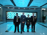 Dr Jane Wang, Profs Waqar Ahmed, Dave Phoenix and Andrei Zvelindovsky in a futuristic building of Shenzhen Virtual University Park in front of the video screen displaying our simulation results.